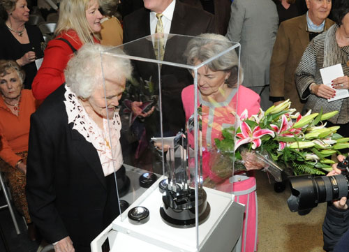 Honoree Ann Boardman (right) looks at the Dyess Trophy while holding flowers that she was presented.